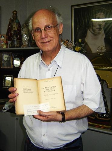 Pe. Júlio com o livro 'Montanha dos Sete Patamares' de Thomas Merton